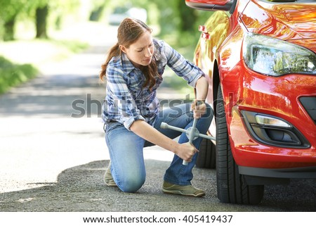Frustrated Female Driver With Tyre Iron Trying To Change Wheel - stock photo