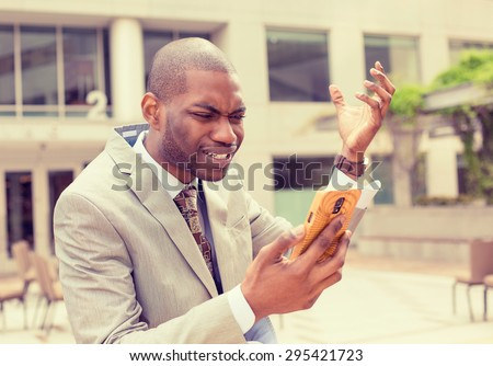 Frustrated handsome young business man in suit receiving bad news message on mobile smart phone standing outdoors outside corporate office  - stock photo