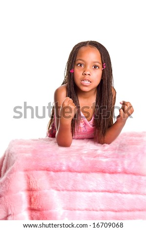 Frustrated little African American girl with finger braids shaking her fists with her elbows on the bed - stock photo