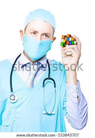 Frustrated Male Medical Surgeon Holding A Jigsaw Cube Searching For A Undiagnosed Cure In A Depiction Of A Doctor Problem Solving A Medical Complication - stock photo