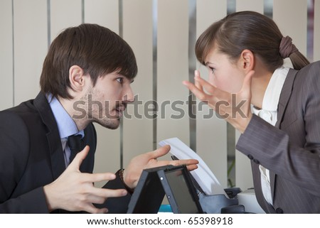 frustrated man and woman discussing by the work in office - stock photo
