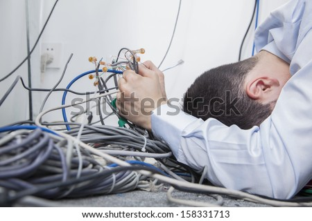Frustrated man lying down trying to figure out and sort computer cables - stock photo