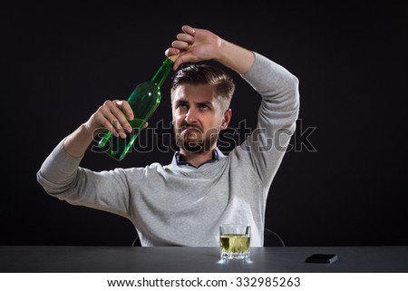 Frustrated Man Opens A Bottle On Black Background - stock photo