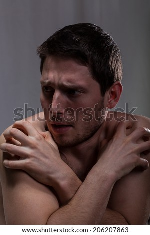 Frustrated man sick on schizophrenia in mental hospital - stock photo