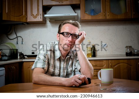 Frustrated man sits in the kitchen in front of a handful of coins and looks at the phone - stock photo