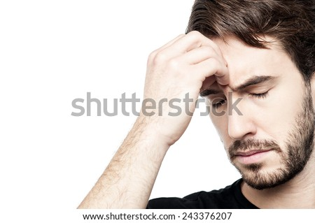 Frustrated man thinking deeply, hand on head. - stock photo