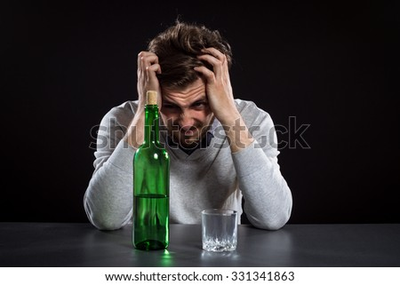 Frustrated Man With Bottle Holding His Head On Black Background - stock photo
