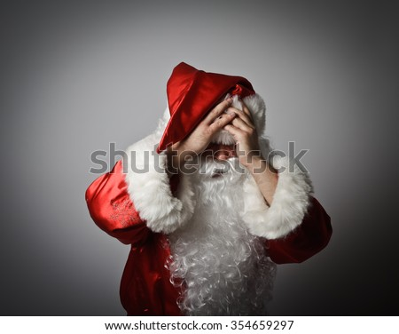 Frustrated Santa Claus. Santa Claus suffering from headache. - stock photo
