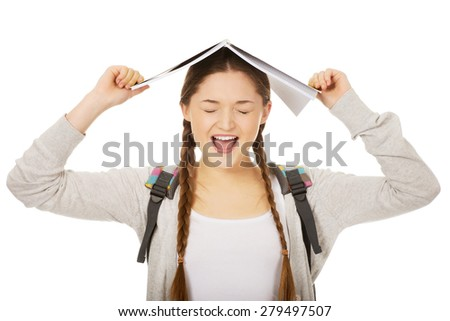 Frustrated teen girl with book over her head. - stock photo