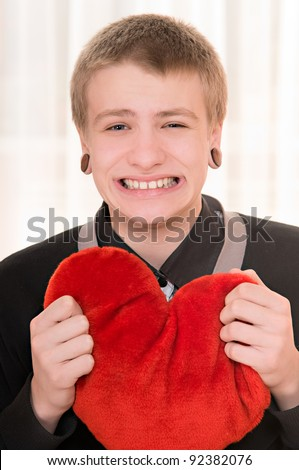 frustrated teenager  with a plush heart in hand - stock photo