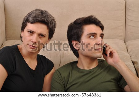 frustrated woman being ignored by a man talking on the cell phone - stock photo