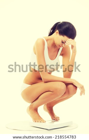Frustrated woman on scale, isolated on white - stock photo