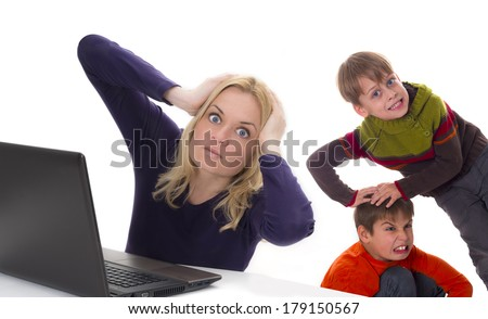 frustrated working mother with fighting kids - stock photo