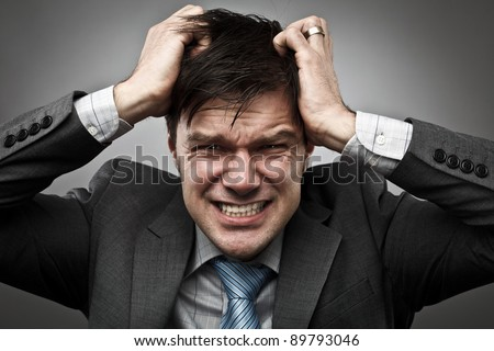 Frustrated young businessman pulling his hair, studio shot - stock photo