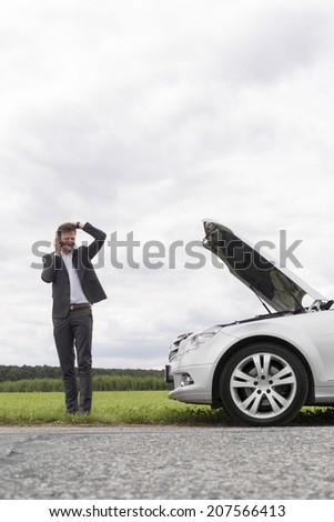 Frustrated young businessman using cell phone near broken down car at countryside - stock photo