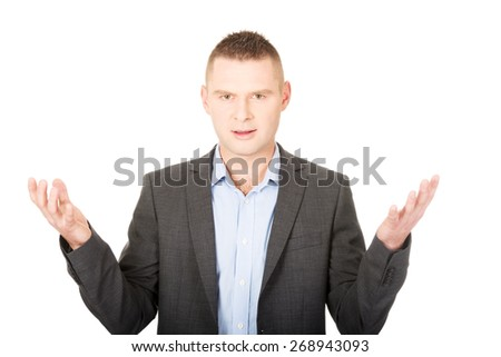Frustrated young businessman with open hands - stock photo