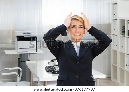 Frustrated young businesswoman suffering from headache in office - stock photo