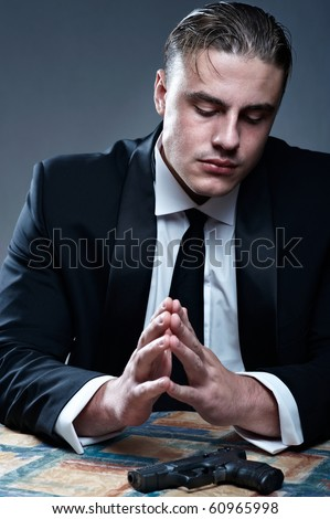 Frustrated young man in suit preparing for suicide. Black gun on table. - stock photo