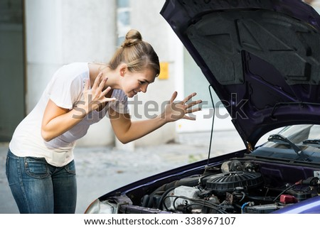 Frustrated young woman looking at broken down car engine on street - stock photo