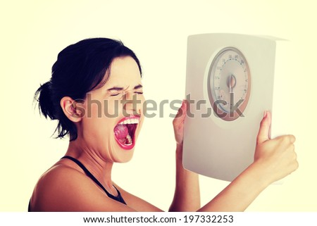 Frustrated young woman with scale. - stock photo