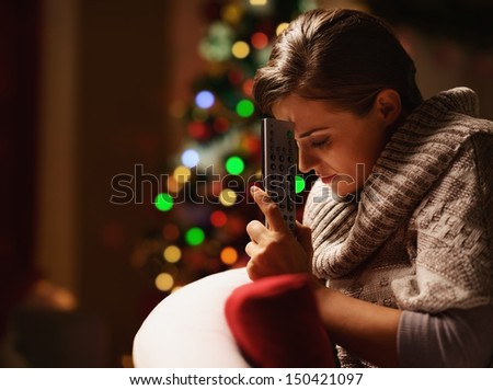 Frustrated young woman with tv remote control in front of christmas tree - stock photo