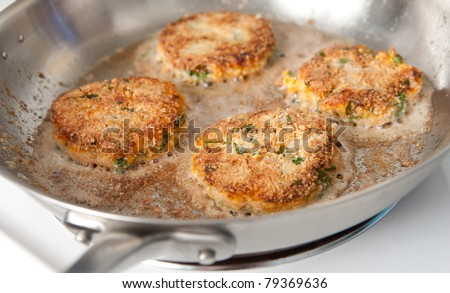 Frying Paleo Style Salmon and Sweet Potato Cakes with Fresh Parsley - stock photo