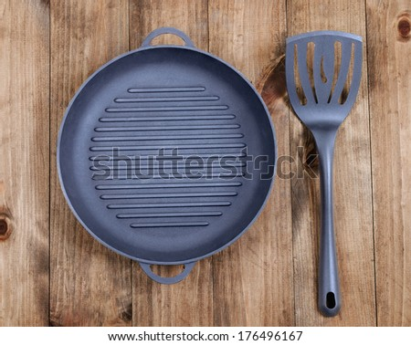 Frying pan and kitchen utensils on wooden table background. View from above - stock photo