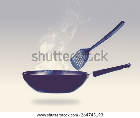 frying pan and smokw in kitchen,vintage color toned image - stock photo