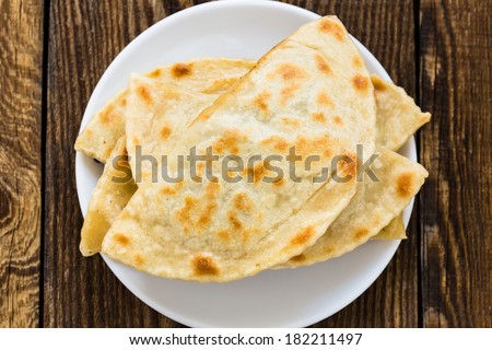 Frying pan baked flat bread on a white plate. Yantyk - traditional Crimean tatar flatbread viewed from above - stock photo