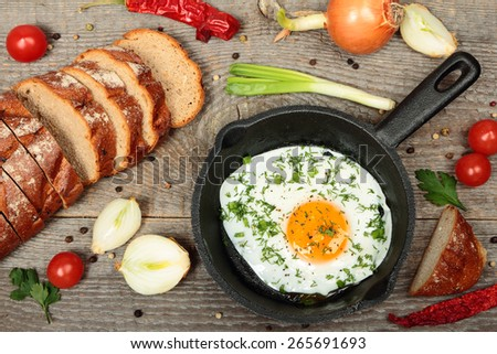 Frying pan with fried egg on old wooden table  - stock photo
