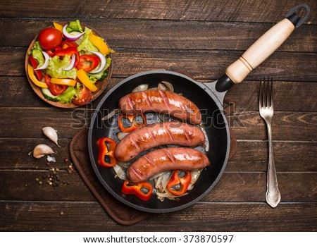 Frying pan with fried sausage and vegetables on a rustic wooden table. Sausages on the grill pan on the wooden background. Top view. - stock photo