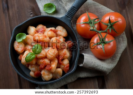 Frying pan with gnocchi in tomato sauce, view from above - stock photo