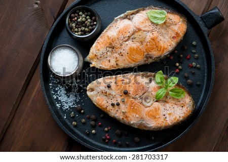 Frying pan with two roasted salmon steaks, view from above - stock photo