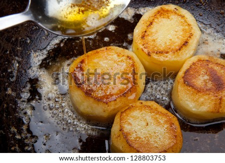 Frying potato slices in a pan browning. - stock photo