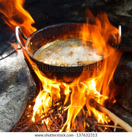 Frying potatoes in a pan over campfire. - stock photo