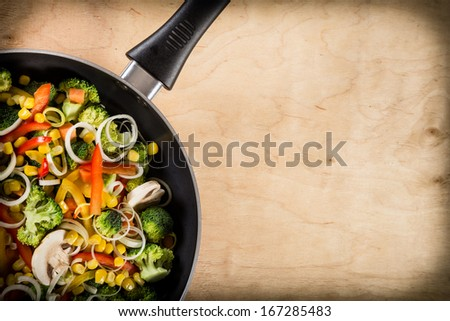 frying vegetables in pan close-up on light wooden background. Space for text - stock photo