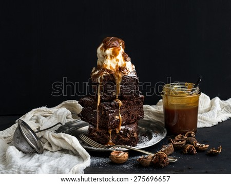 Fudgy Brownies tower with salted caramel, walnuts and ice-cream on vintage metal plate. Dark backdrop - stock photo