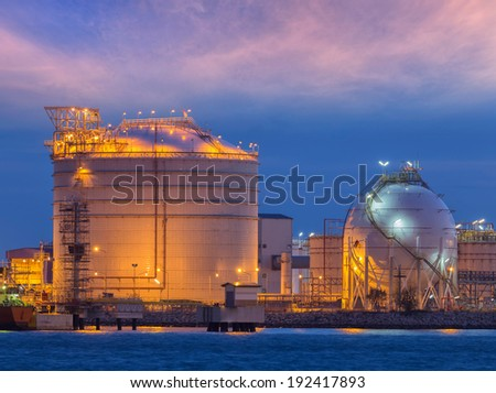 Fuel and cargo complex in port at twilight time - stock photo