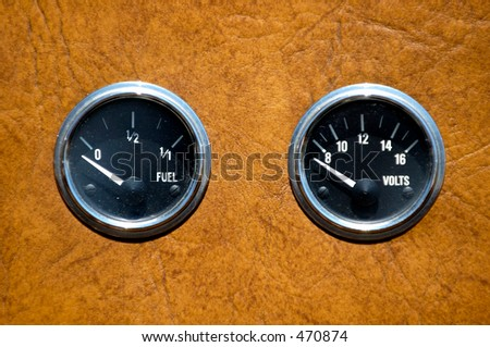 Fuel gauge and voltmeter on vintae car instruments panel - stock photo