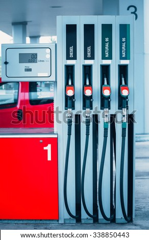 Fuel guns at gas station with petrol and diesel fuel for automobile transport - stock photo
