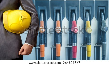 fuel nozzle at gas station. Petrol station. Filling station. Petrol. Gasoline. Man work Engineer hand hold yellow helmet for workers security construction worker No face person - stock photo