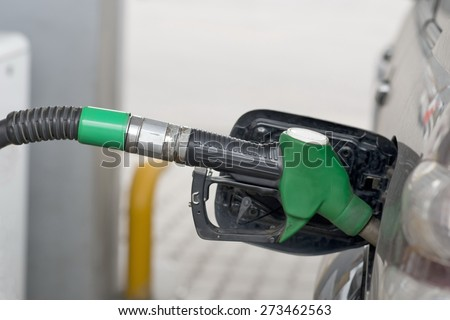 Fuel nozzle during refueling at a gas station. - stock photo