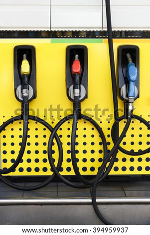 Fuel nozzle in gas station.Another color of fuel nozzle for  benzine,gasoline and diesel. - stock photo