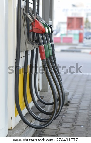 Fuel nozzles at a gas station. - stock photo