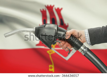 Fuel pump nozzle in hand with flag on background - Gibraltar - stock photo