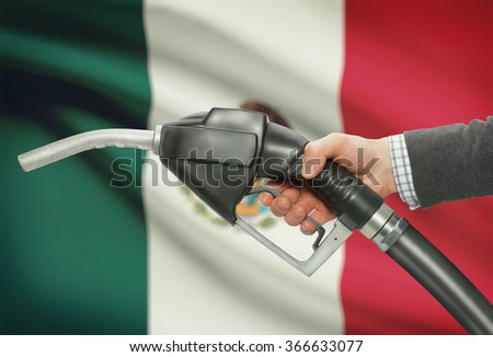Fuel pump nozzle in hand with flag on background - Mexico - stock photo