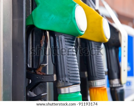 Fuel pump nozzles in a gas station - stock photo