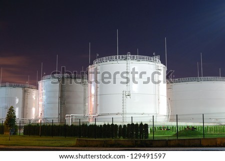 Fuel storage tanks at oil terminal by night - stock photo