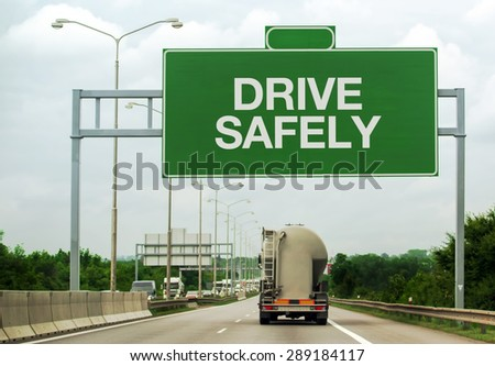 Fuel Tanker Truck on Highway Road Passing by Drive Safely Sign as a Reminder for Safety in Traffic and Accident Prevention Concept. - stock photo