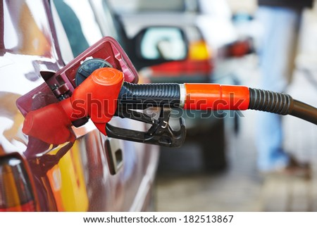 Fuel theme. dispenser pumping diesel or gasoline in car at gas station - stock photo